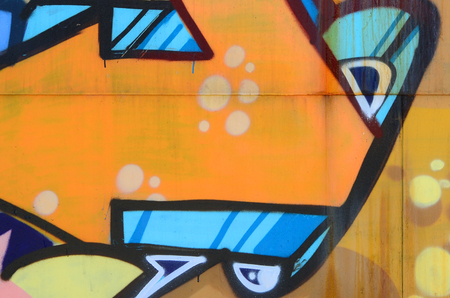 Street art. Abstract background image of a fragment of a colored graffiti painting in beige and orange tones.
