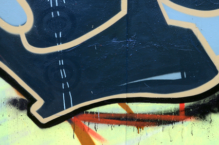 Street art. Abstract background image of a fragment of a colored graffiti painting in dark grey and red tones. Stock Photo