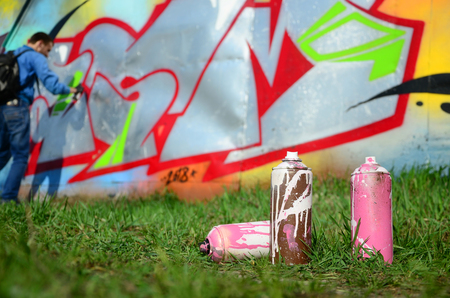 A few used paint cans against the background of the space with the wall on which the young guy draws a large graffiti drawing. Modern art of drawing walls in graffiti.