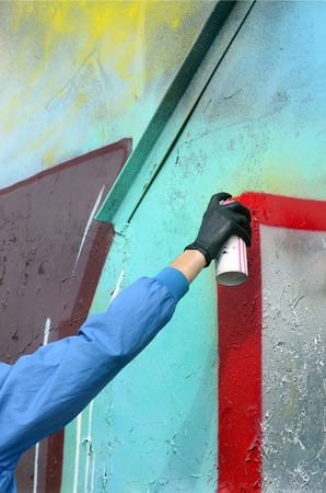 A hand with a spray can that draws a new graffiti on the wall. Photo of the process of drawing a graffiti on a metal wall. The concept of street art and illegal vandalism.