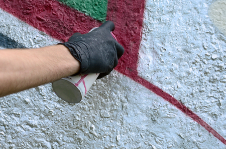A hand in black gloves paints graffiti on a concrete wall. Illegal vandalism concept. Street art. Stok Fotoğraf
