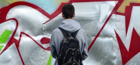 A young graffiti artist with a black bag looks at the wall with his graffiti on a wall. Street art concept.