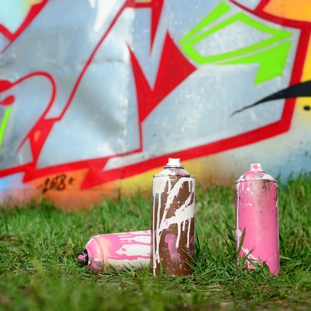 A few used paint cans lie on the ground near the wall with a beautiful graffiti painting. Street art and vandalism concept.