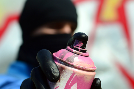 A young graffiti artist in a blue jacket and black mask is holding a can of paint in front of him against a background of colored graffiti drawing. Street art and vandalism concept.
