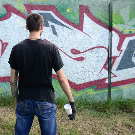 A young hooligan with a spray can stands against a concrete wall with graffiti paintings. Illegal vandalism concept. Street art.