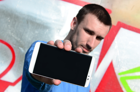 The graffiti artist demonstrates a smartphone with an empty black screen against the background of a colorful painted wall. Street art concept.