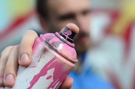 A young graffiti artist in a blue jacket is holding a can of paint in front of him against a background of colored graffiti drawing. Street art and vandalism concept.