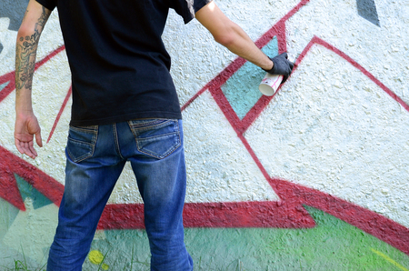 A young hooligan paints graffiti on a concrete wall. Illegal vandalism concept. Street art.