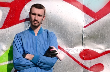 The graffiti artist with spray can poses against the background of a colorful painted wall. Street art concept.