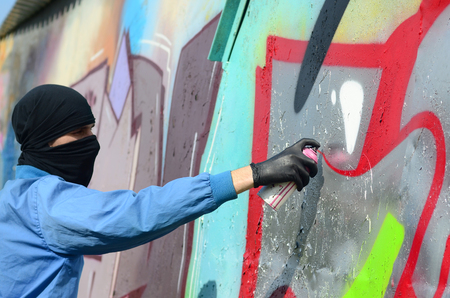 A young hooligan with a hidden face paints graffiti on a metal wall. Illegal vandalism concept. Stock Photo