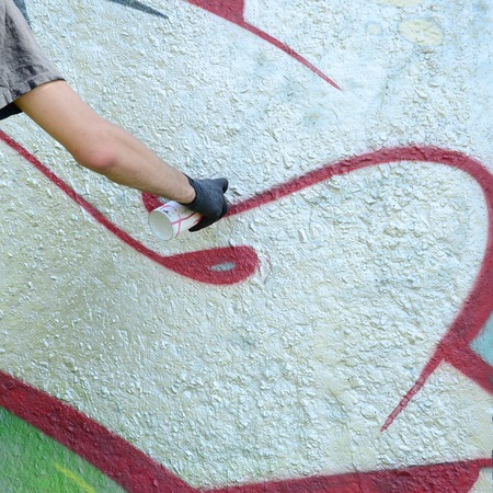 A hand in black gloves paints graffiti on a concrete wall. Illegal vandalism concept. Street art. Stock Photo