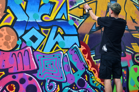 KHARKOV, UKRAINE - MAY 27, 2017: Festival of street arts. Young guys draw graffiti on portable wooden walls in the center of the city. The process of painting on walls with aerosol spray cans