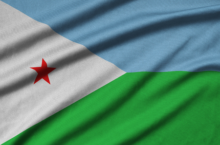 Djibouti flag  is depicted on a sports cloth fabric with many folds. Sport team waving banner Stock Photo