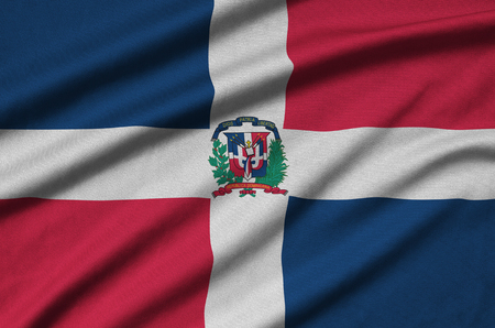 Dominican Republic flag  is depicted on a sports cloth fabric with many folds. Sport team waving banner Stock fotó