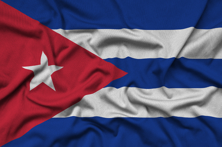 Cuba flag  is depicted on a sports cloth fabric with many folds. Sport team waving banner Imagens