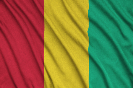 Guinea flag  is depicted on a sports cloth fabric with many folds. Sport team waving banner