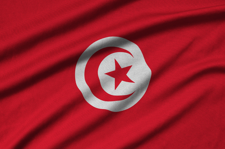 Tunisia flag  is depicted on a sports cloth fabric with many folds. Sport team waving banner Фото со стока