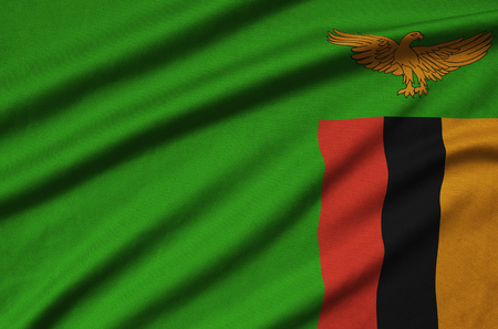 Zambia flag  is depicted on a sports cloth fabric with many folds. Sport team waving banner