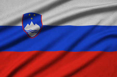 Slovenia flag  is depicted on a sports cloth fabric with many folds. Sport team waving banner Banco de Imagens
