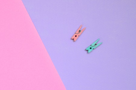 Two colored wooden pegs lie on texture background of fashion pastel violet and pink colors paper in minimal concept. Stock Photo