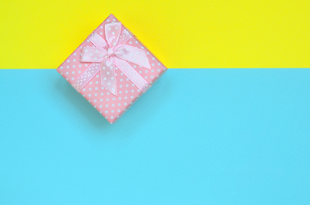Small pink gift box lie on texture background of fashion pastel blue and yellow colors paper in minimal concept. Stock Photo