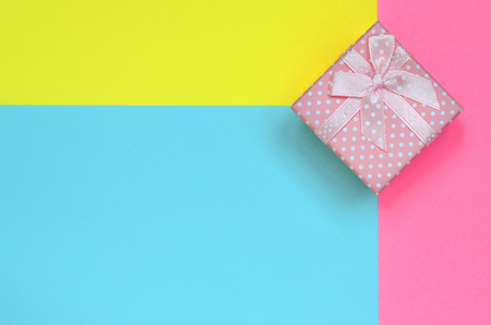 Small pink gift box lie on texture background of fashion pastel blue, yellow and pink colors paper in minimal concept. Stock Photo