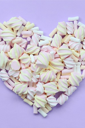 Colorful marshmallow laid out on violet and pink paper background. pastel creative textured heart. minimal.