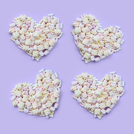 Colorful marshmallow laid out on violet and pink paper background. pastel creative textured hearts. minimal. Stock Photo