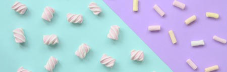 Colorful marshmallow laid out on violet and blue paper background. pastel creative textured pattern. minimal.