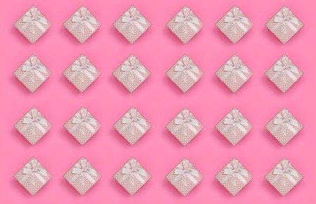 A lot of pink gift boxes lies on texture background of fashion pastel pink color paper in minimal concept. Abstract trendy pattern.