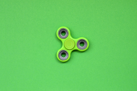 Green fidget spinner lies on texture background of fashion pastel green color paper in minimal concept.