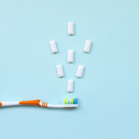 Toothbrush and chewing gums lie on a pastel blue background. Top view, flat lay. Minimal concept.