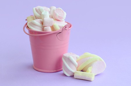 A miniature pink bucket filled with marshmallow lies on a violet pastel background. Minimal concept.
