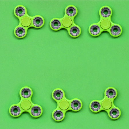 Many green fidget spinners lies on texture background of fashion pastel green color paper in minimal concept.