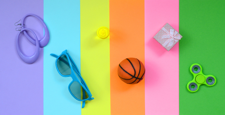 Trendy fashionable pastel composition with earrings, sunglasses, beverage can, basketball ball, gift box and spinner on background of pink, violet, green, orange, yellow and blue colors.
