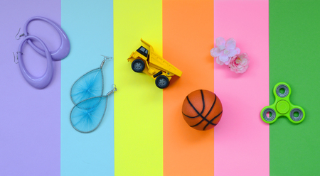 Trendy fashionable pastel composition with earrings, sunglasses, beverage can, basketball ball, toy truck, flower and spinner on background of pink, violet, green, orange, yellow and blue colors.