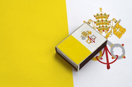 Vatican City State flag  is pictured on a matchbox that lies on a large flag. Stock Photo
