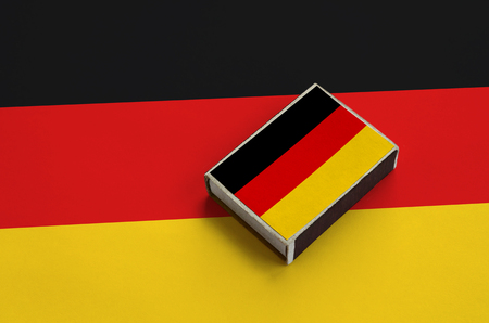 Germany flag  is pictured on a matchbox that lies on a large flag.