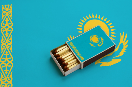 Kazakhstan flag  is shown in an open matchbox, which is filled with matches and lies on a large flag. Stock Photo