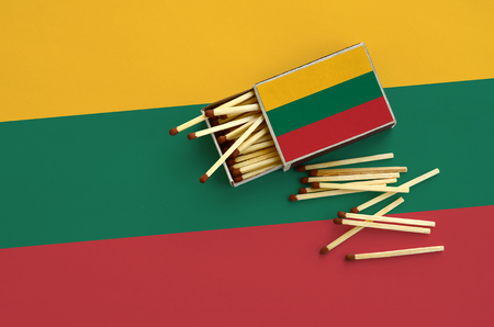 Lithuania flag  is shown on an open matchbox, from which several matches fall and lies on a large flag.