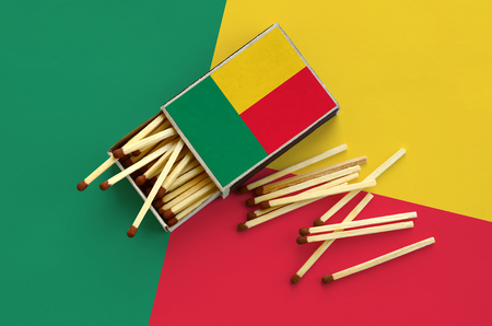 Benin flag  is shown on an open matchbox, from which several matches fall and lies on a large flag. Stock Photo