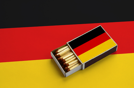 Germany flag  is shown in an open matchbox, which is filled with matches and lies on a large flag.