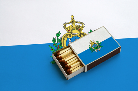 San Marino flag  is shown in an open matchbox, which is filled with matches and lies on a large flag. Reklamní fotografie