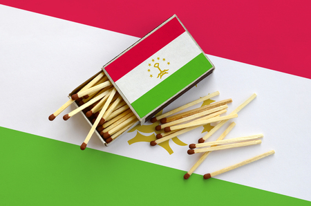 Tajikistan flag is shown on an open matchbox, from which several matches fall and lies on a large flag.
