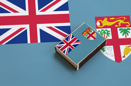 Fiji flag  is pictured on a matchbox that lies on a large flag. Stock Photo