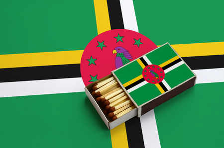 Dominica flag  is shown in an open matchbox, which is filled with matches and lies on a large flag.