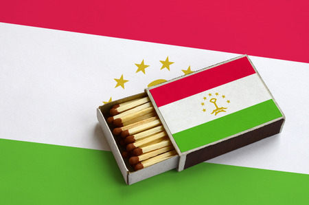 Tajikistan flag is shown in an open matchbox, which is filled with matches and lies on a large flag.