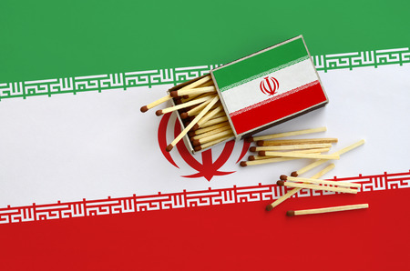 Iran flag  is shown on an open matchbox, from which several matches fall and lies on a large flag.
