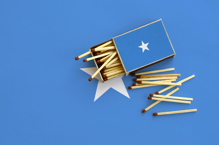 Somalia flag  is shown on an open matchbox, from which several matches fall and lies on a large flag. Stock Photo