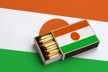Niger flag  is shown in an open matchbox, which is filled with matches and lies on a large flag.